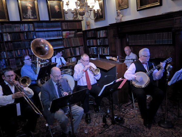The John Gill Jazz Band: L-R: Jim Fryer (tmbn), Brian Nalepka (bs), Dan Block (cl), Kevin Dorn (dr), Simon Wettenhall (tmpt) Conal Fowkes (p) and John (bnj,voc, bandleader) in the Library